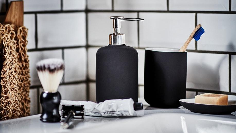 Seifenspender, Zahnputzbecher und Seifenschale der Serie EKOLN in der Farbe Anthrazit stehen gruppiert auf einem weißen Waschbecken mit einem Rasierschaumpinsel und einem Rasierer, sowie einer Tube Rasiercreme.