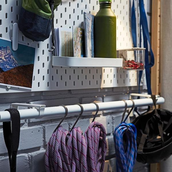 Seile und Kletterutensilien hängen von Haken an IKEA HUGAD Gardinenstange weiß