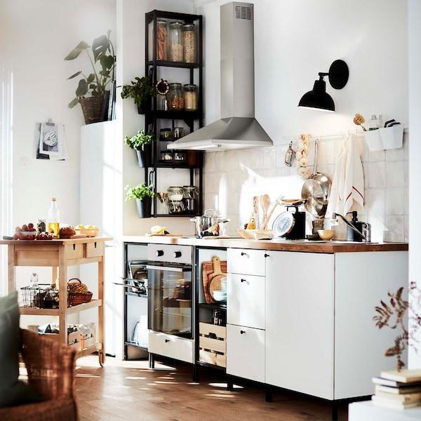 Seinään kiinnitettävät RYTMISK-liesituuletin ja SKURUP-valaisin säästävät tilaa vaaleassa ENHET keittiössä.