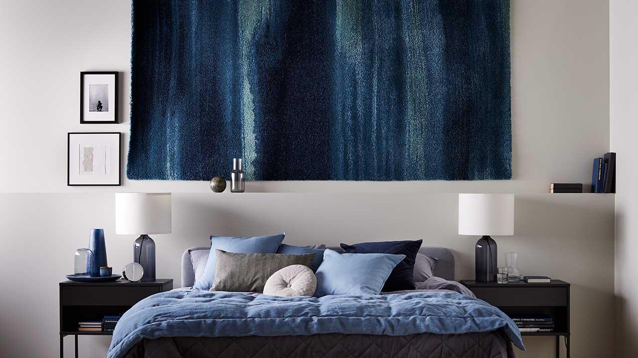 Seinällä matto, VIKHAMMER-yöpöydät vaaleanharmaan SLATTUM-parisängyn molemmin puolin, sekä KOPPARBLAD-vuodevaatteet.