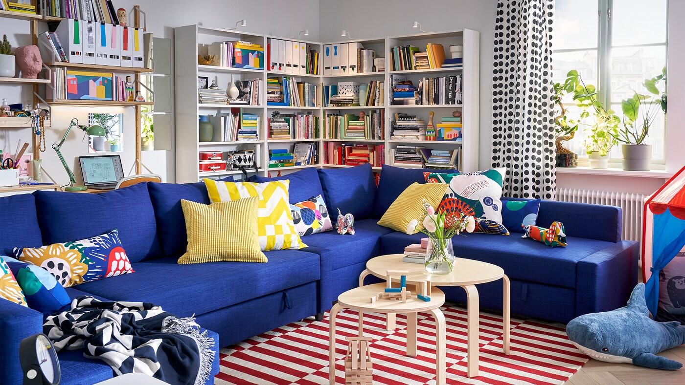 Séjour avec canapé convertible d'angle FRIHETEN bleu agrémenté de nombreux coussins, bibliothèques, fenêtre et plantes sur l'appui de fenêtre.