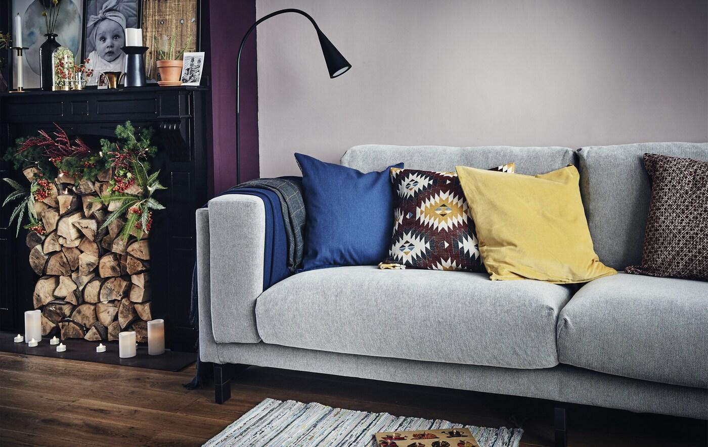 Séjour avec canapé gris, luminaire et cheminée remplie de bûches.