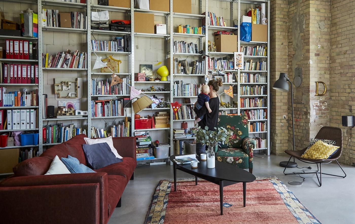 Séjour avec canapé rouge et mur d'étagères.