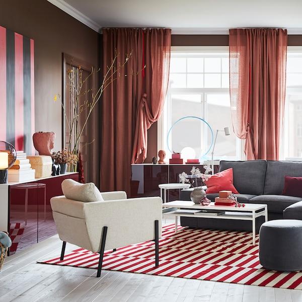 Séjour avec rideaux brun-rose, tapis rouge/blanc, canapé gris et armoires murales aux portes en rouge brillant.