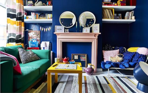 Séjour coloré avec murs bleus et canapé vert.