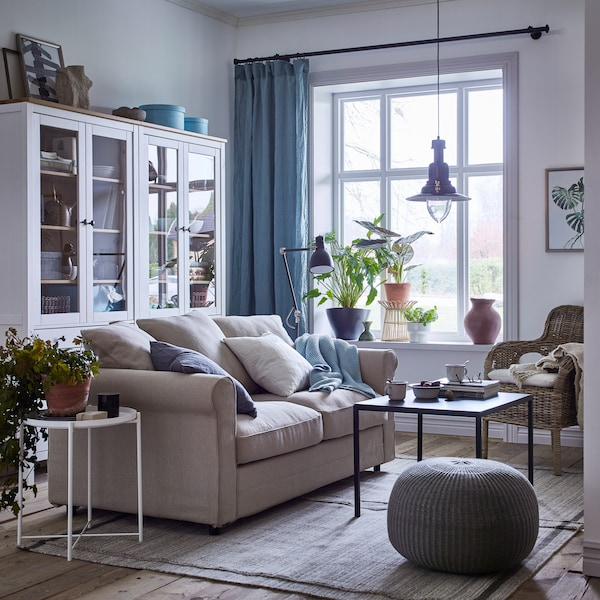 Séjour cosy en beige et blanc avec rideaux bleus, garni d'un canapé 2 places GRÖNLID avec revêtement Sporda naturel, d'un fauteuil en rotin et de vitrines.
