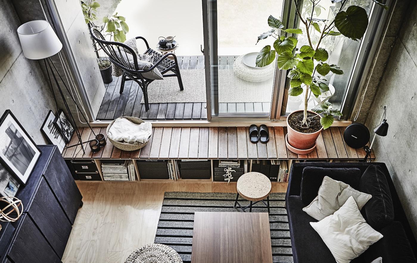 Séjour en gris et blanc, avec terrasse et portes-fenêtres.