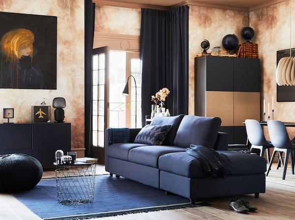 Séjour équipé d'un canapé convertible 3 places VIMLE avec housse ORRSTA en bleu-noir et de quelques armoires et sièges. Des portes ouvertes donnent sur une terrasse.