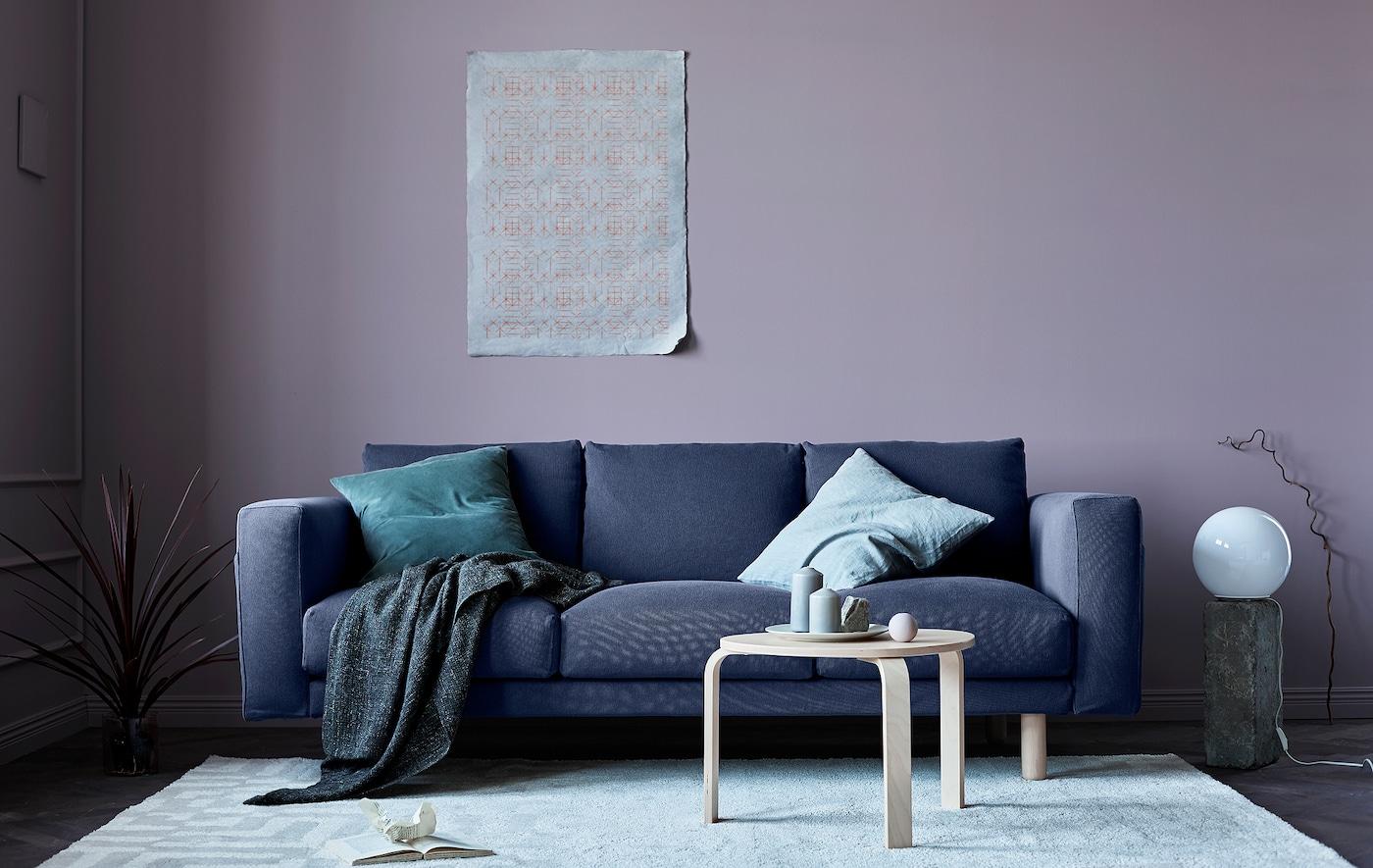 Séjour relooké pour l'automne avec canapé gris, murs roses, couvertures et éléments naturels.