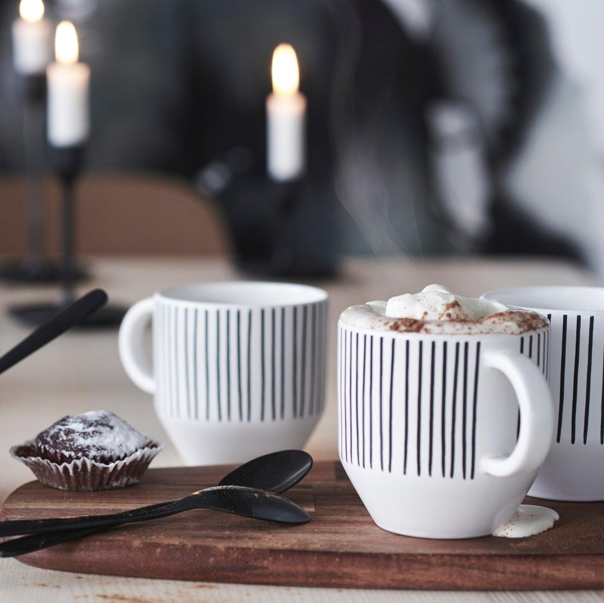 Selbst bemalte Tassen auf einem Tablett aus Holz vor einem Kerzenständer