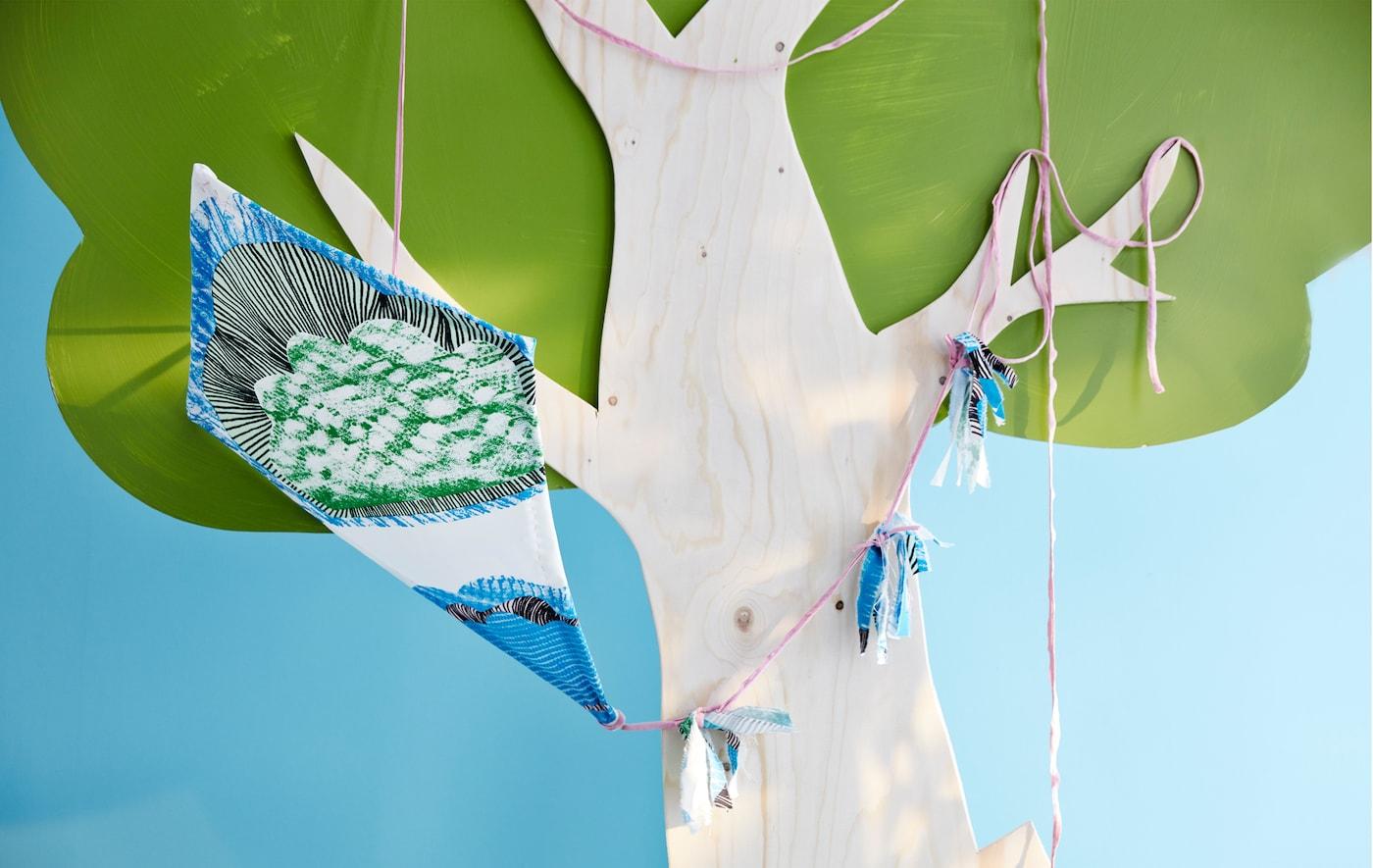 Selbst gebastelter blau, weiß & grüner Drachen in einem Baum.