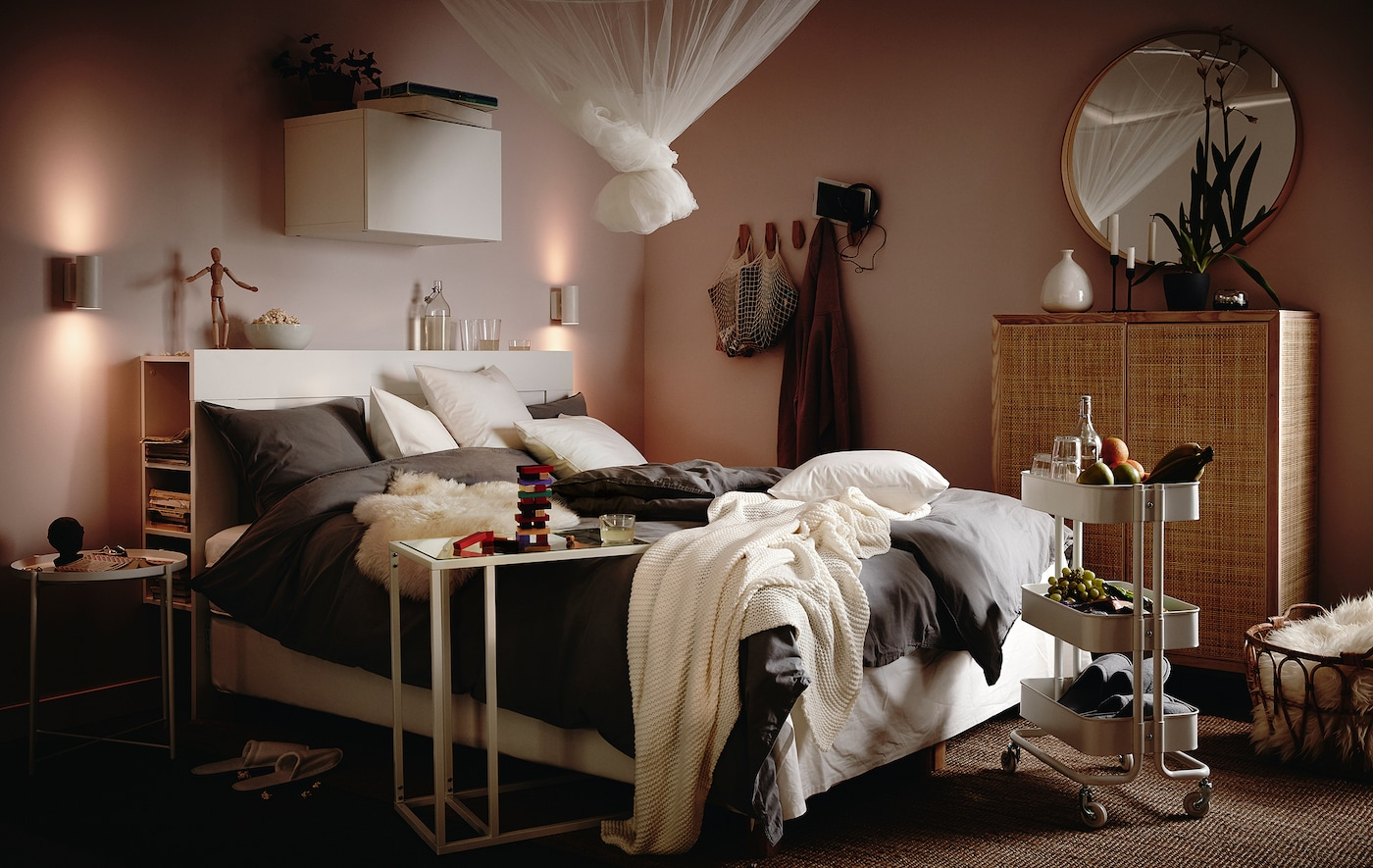 Seng med blødt sengetøj, puder og plaider, et rullebord med snacks og drikkevarer ved siden af sengen og et myggenet bundet op med en knude oven over den.