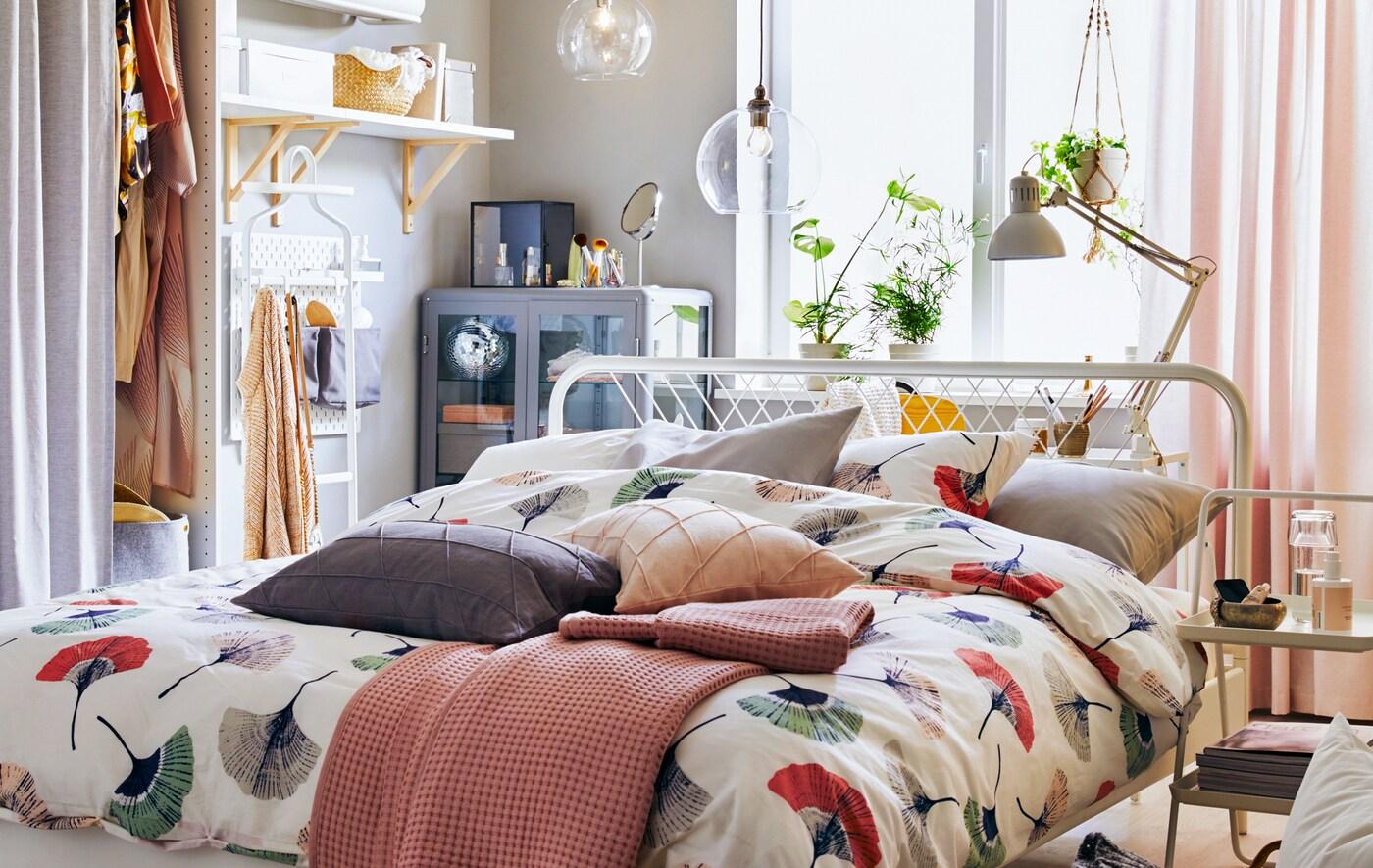 Seng med blomstret sengetøj midt i et rum med opbevaring og hylder langs med væggene.