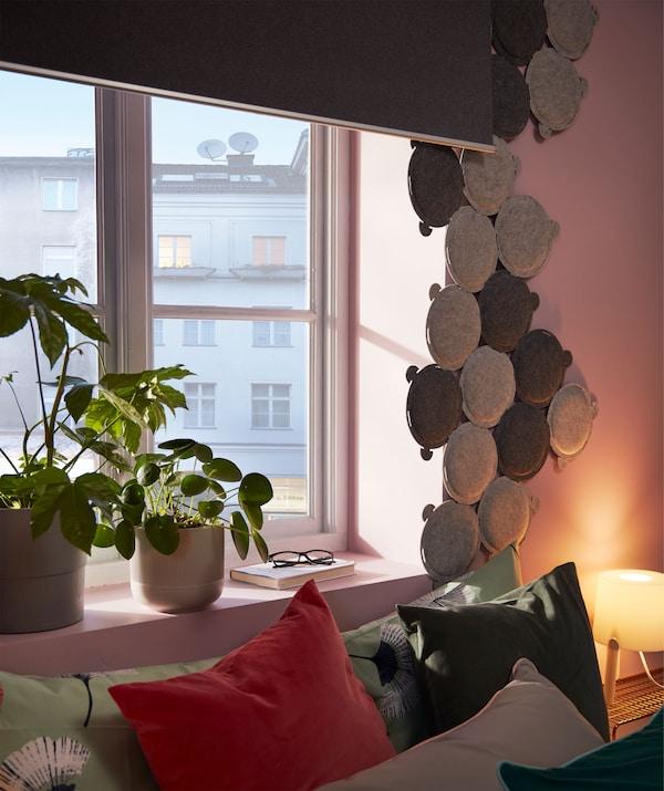 Seng under et vindue med mørklægningsrullegardin. Vinduet er indrammet af masser af små, runde lydabsorberende paneler.