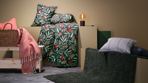 Sengetøj, en plaid og et tæppe ligger draperet over små forhøjninger og en bænk.