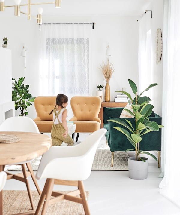 Seorang budak perempuan berlari merentasi ruang makan/ruang tamu pelan terbuka dengan sofa baldu berwarna hijau, kerusi malas berwarna mustard dan kerusi meja makan berwarna putih.