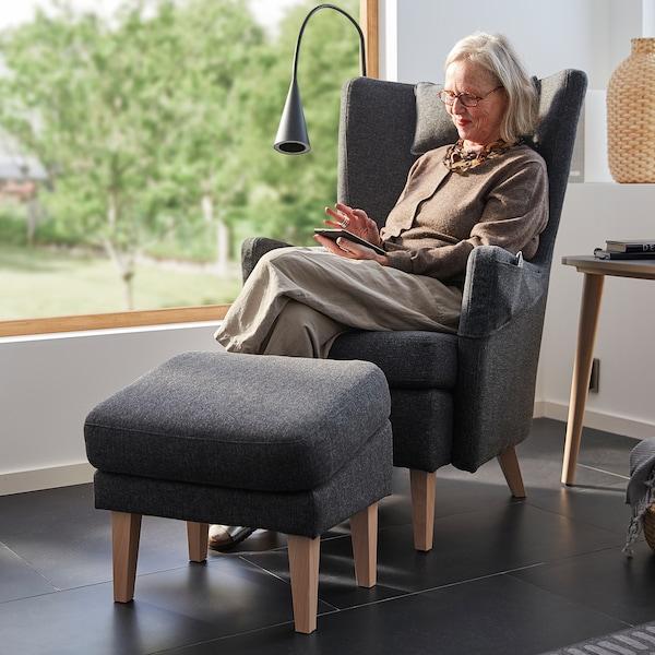 Seorang wanita berusia dalam lingkungan 60-an duduk di atas kerusi berlengan OMTÄNKSAM. Kerusi berlengan dan bangku kaki tersebut ditempatkan di hadapan tingkap besar.