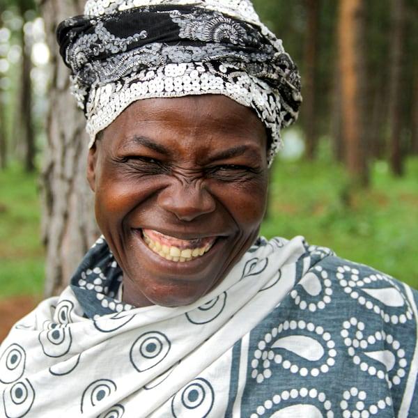 Seorang wanita Uganda, tersenyum lebar, yang terlibat dalam projek White Nile.