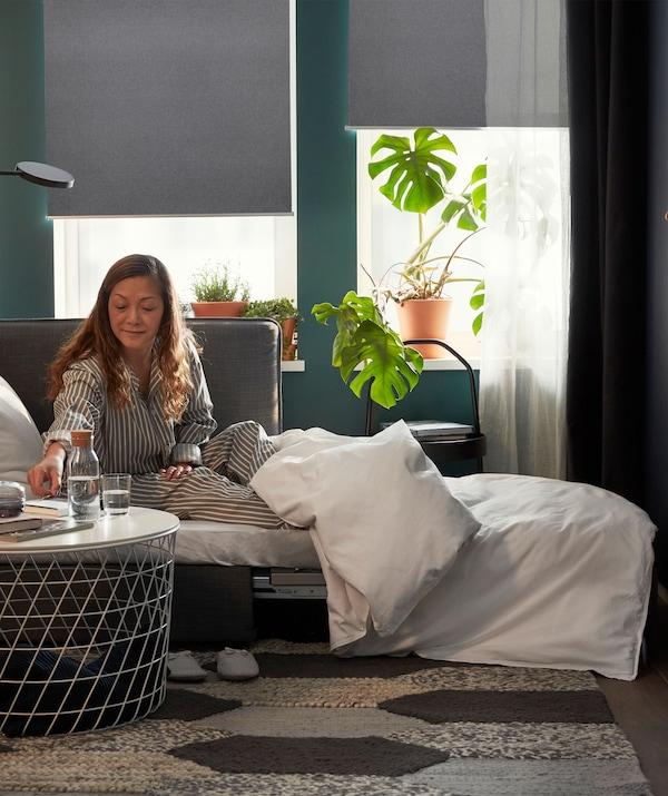 Seorang wanita yang memakai pijama sedang duduk di atas katil sofa yang digunakan sebagai katil, gelas air di atas meja kopi, bidai bergulung separuh tertutup di bahagian belakang.