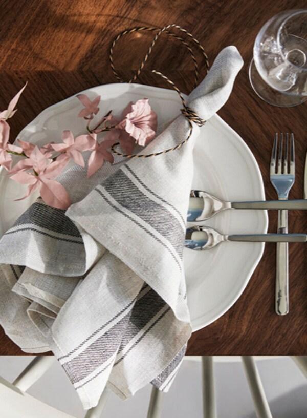 Serviette de table enroulée et attachée avec des fleurs artificielles roses
