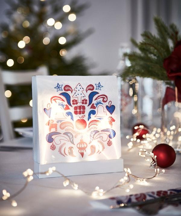 Serviettes en papier à motif festif dans un support éclairé, qui contribue au décor de la table de fête.