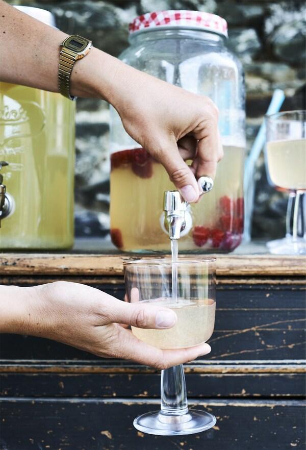 Servindo unha bebida nun vaso dende unha xerra con tapa.