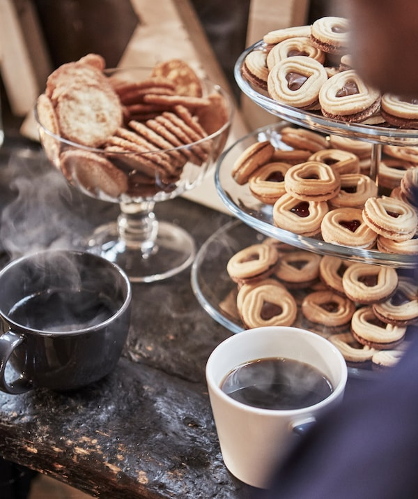 Сервировочный поднос с тремя ярусами, заполненный печеньем в форме сердца. Рядом стоят две кружки горячего кофе и миска с круглыми печеньями.