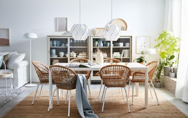 Šest jedinstvenih, ručno ispletenih IKEA NILSOVE stolica od ratana s naslonima za ruke postavljeno je oko blagovaonskog stola u dnevnoj sobi otvorena plana.