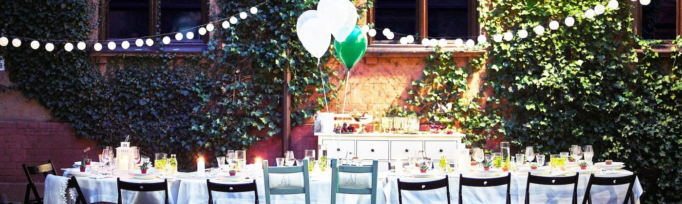 Set table with chairs, light cords and balloons in the garden