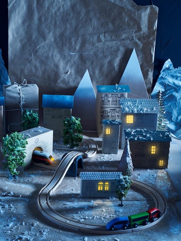 Set trenino LILLABO all'interno di una scenografia in cartone che raffigura una città di notte con le luci gialle alle finestre.