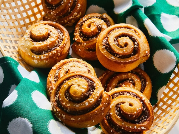 Several cinnamon buns are placed inside a basket.
