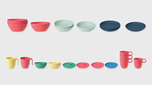Several colorful bowls, plates, and cups lined up in a row against a gray background.