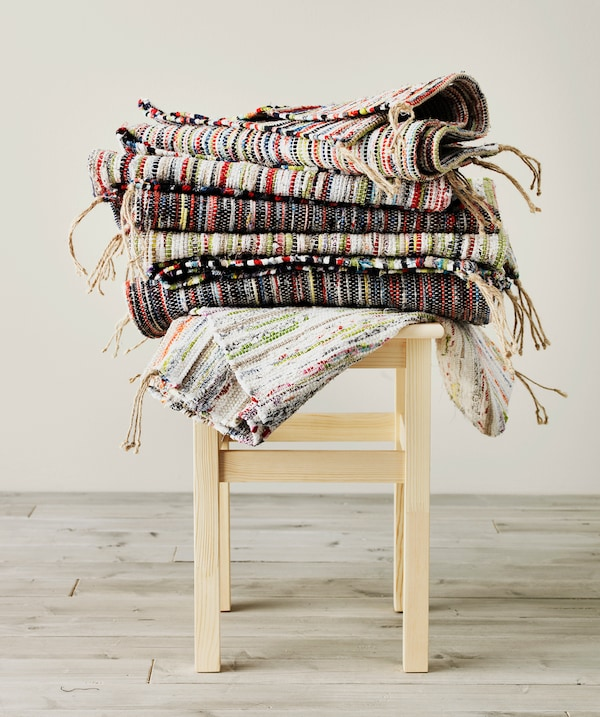Several colourful TÅNUM rugs stacked on a small stool.