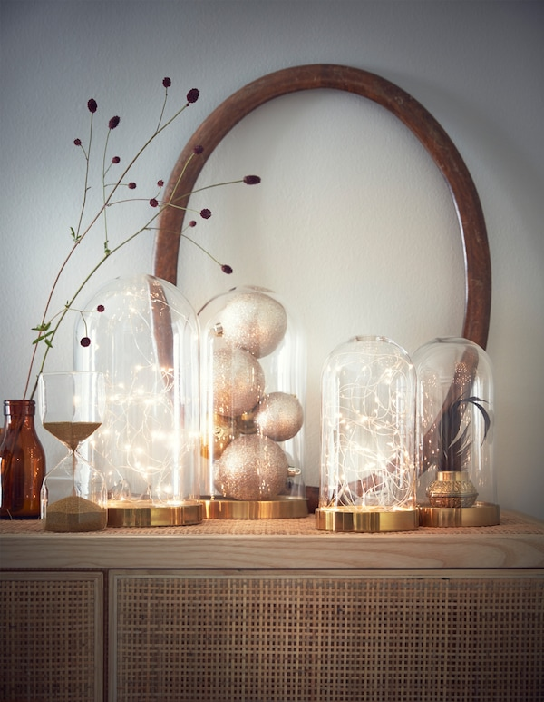 Several decorative glass domes filled with battery powered light chains, baubles and a plant on a cabinet.