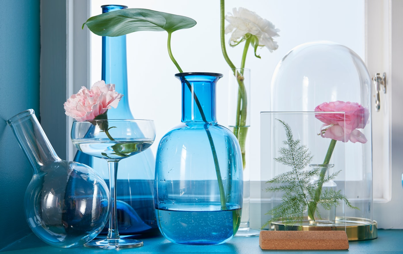 Several different shaped blue and clear glass vases and an IKEA BEGÅVNING glass dome on a window sill.