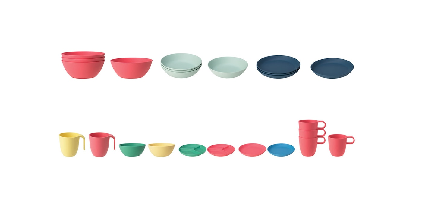 Several green, yellow, pink, and blue bowls, plates, and cups from the HEROISK series lined up against a white background.