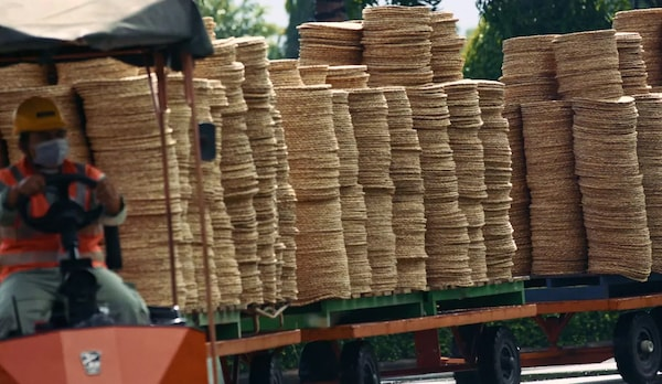 Several high stacks of a brown, round placemat sitting on a truck ready for transport.