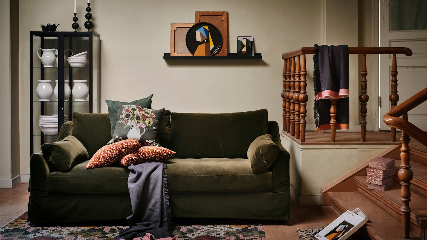 Several items from the IKEA DEKORERA collection stand in a traditional, green-coloured living room with a warm look.