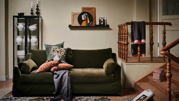 Several items from the IKEA DEKORERA collection stand in a warm living room, with a dark green sofa with cushions.
