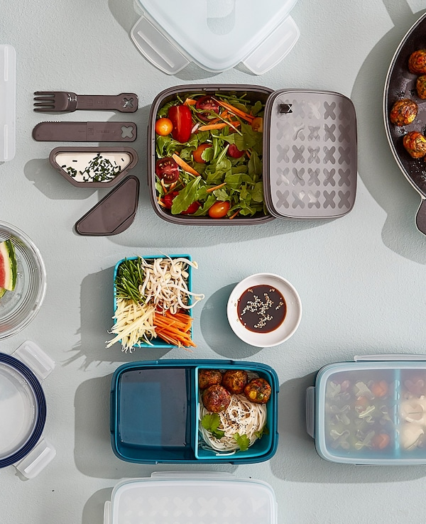 Several lunch boxes on a worktop showing options for removable compartments for separating food types.