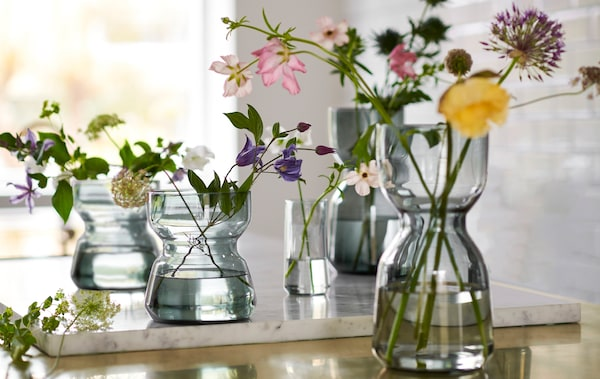 Several OMTÄNKSAM glass vases, with characteristic waists to facilitate grip, standing on a worktop, fresh flowers in each.