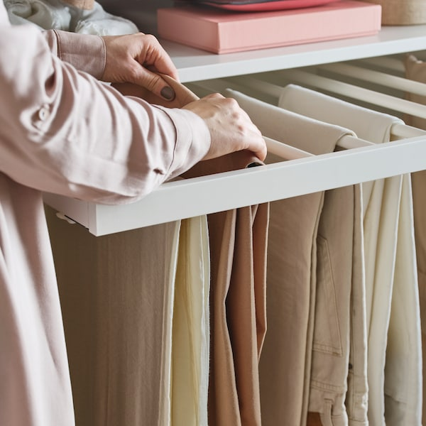 Several pairs of beige pants on a KOMPLEMENT pull-out trouser hanger, someone in a pink shirt adjusts one of the pairs.