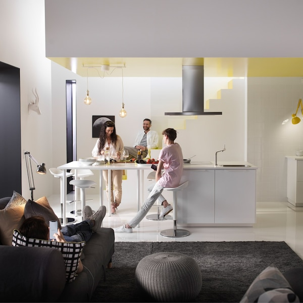 Several people seated and standing around an open living space, with the kitchen area the main focus.
