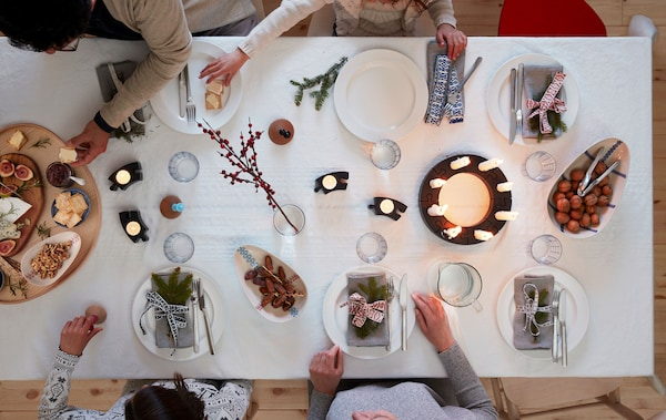 Several persons seated around a table set for a festive occasion: napkins, decorations, lit LED candles, cheese platter.
