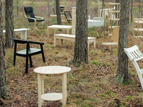 Several side tables, chairs, and benches in a forest of trees.