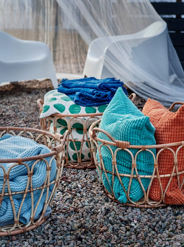 Several SNIDAD rattan baskets standing on gravel, filled with INGABRITTA throws, GULLKLOCKA cushions and other textiles.