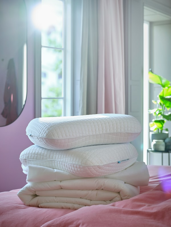 Several stacked pillows, on top there is the ergonomic pillow KLUBBSPORRE.