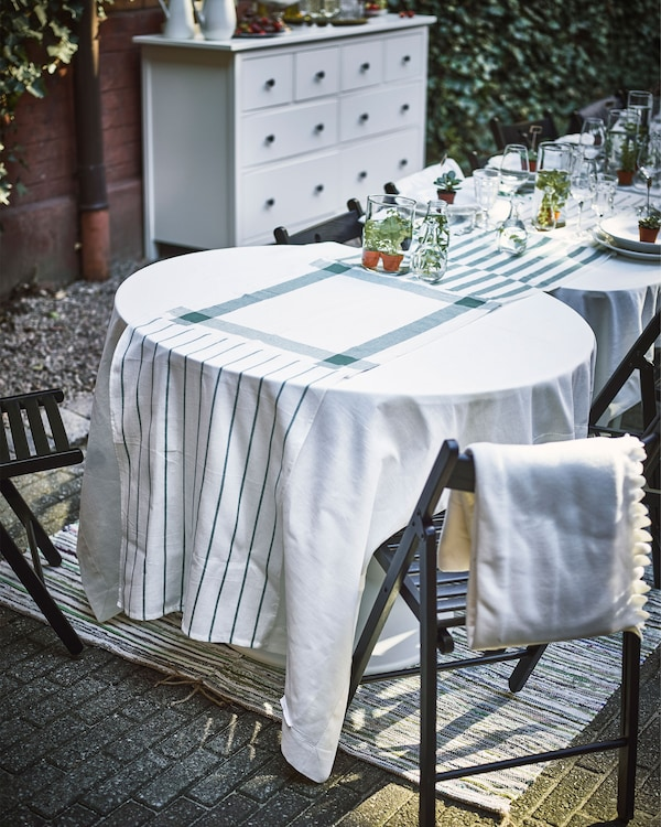 Several tables of different shapes and sizes sit in a row, with white tablecloths and a table runner made of white and green dish towels.