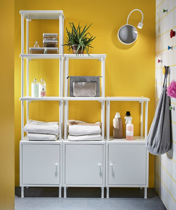 Several white IKEA DYNAN shelf units, in a yellow bathroom, used for storing and displaying towels and cosmetics.