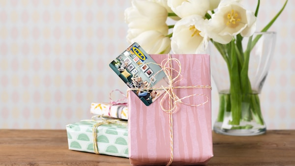 Several wrapped gifts stand next to a vase of flowers on a table. An IKEA gift card is attached to one of them.